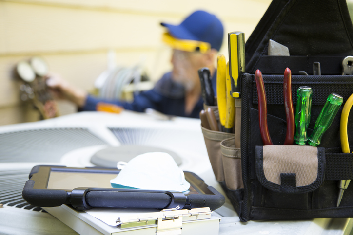 A contractor's tool bag beside tablet device sits atop AC unit