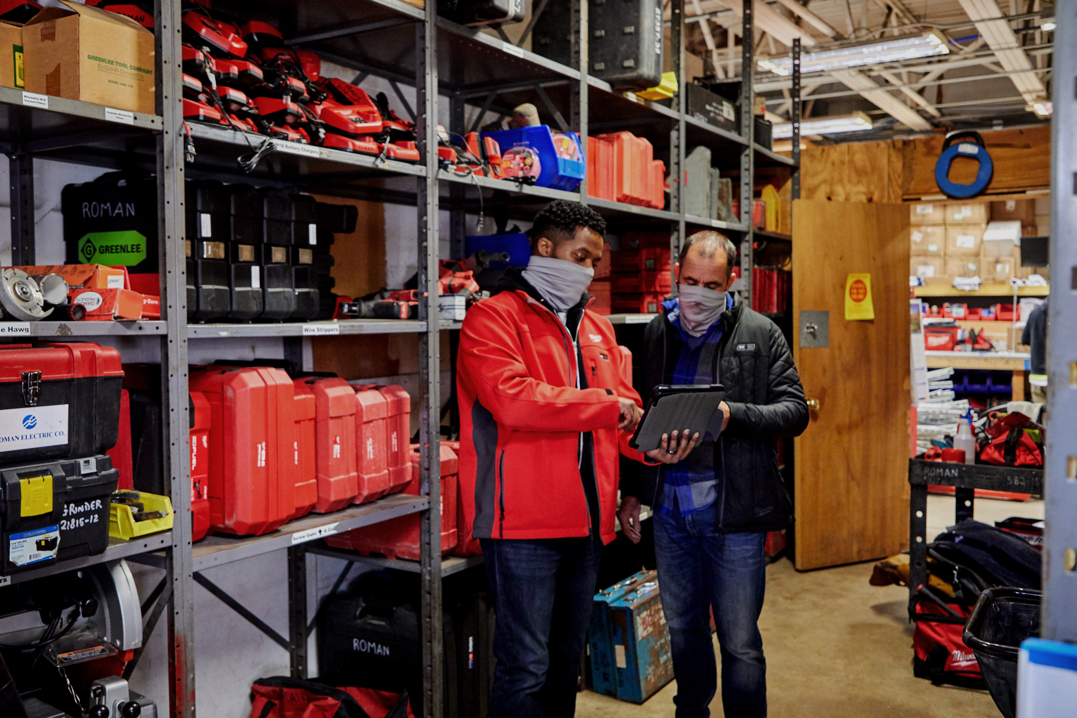 Two inventory managers consult over tablet device in tool crib