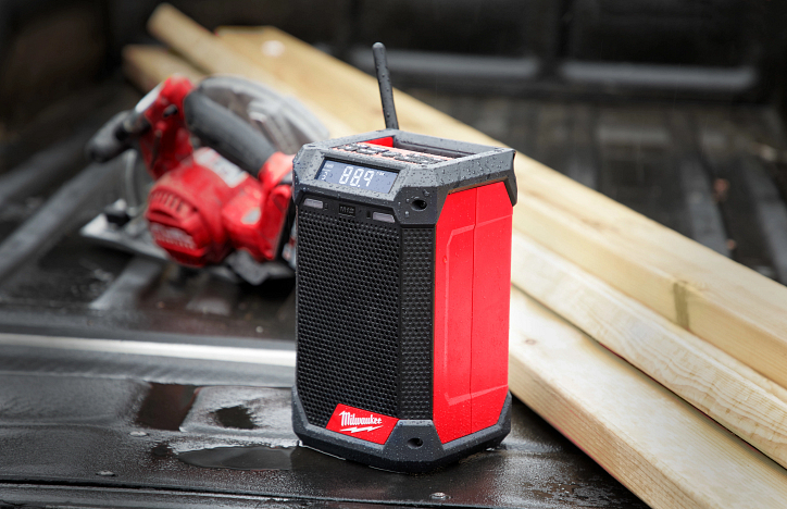 A Milwaukee jobsite radio sits in a pickup truck bed glazed with rainwater beside two-by-fours and a red circular saw
