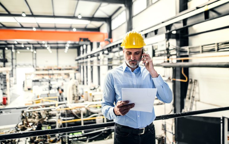 A manufacturing plant manager in hard hat reviews document while speaking on cellphone
