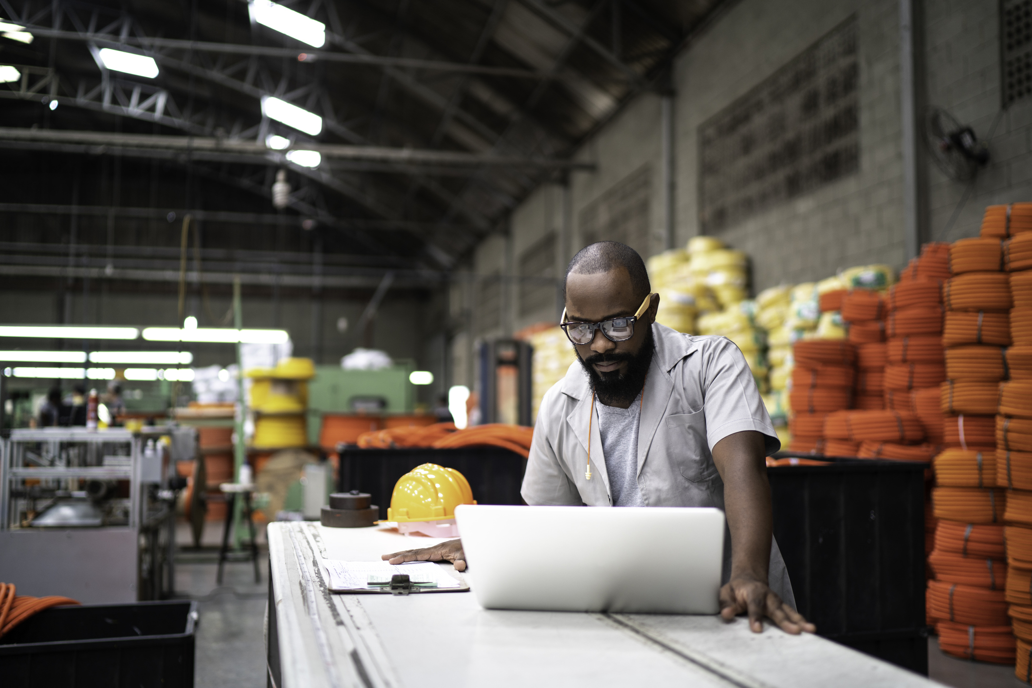 A manufacturing engineer in factory reviews work plans on laptop