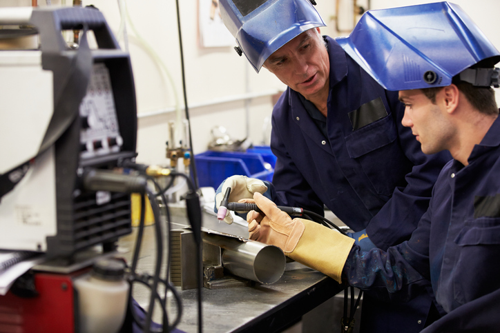 A metalworking trade mentors apprentice in welding and fabrication