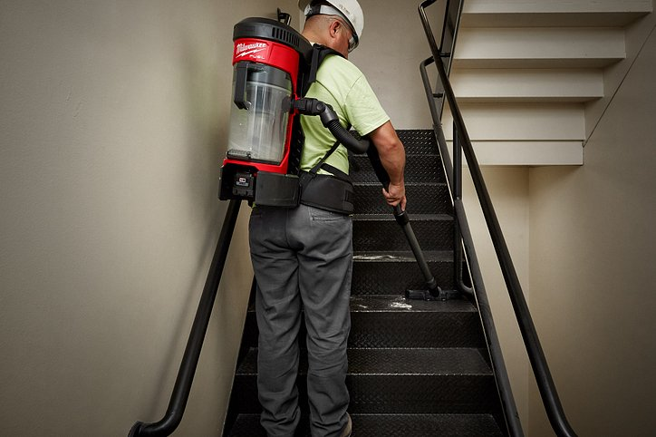 Milwaukee M18 3-in-1 vacuum is used as backpack as contractor cleans industrial staircase
