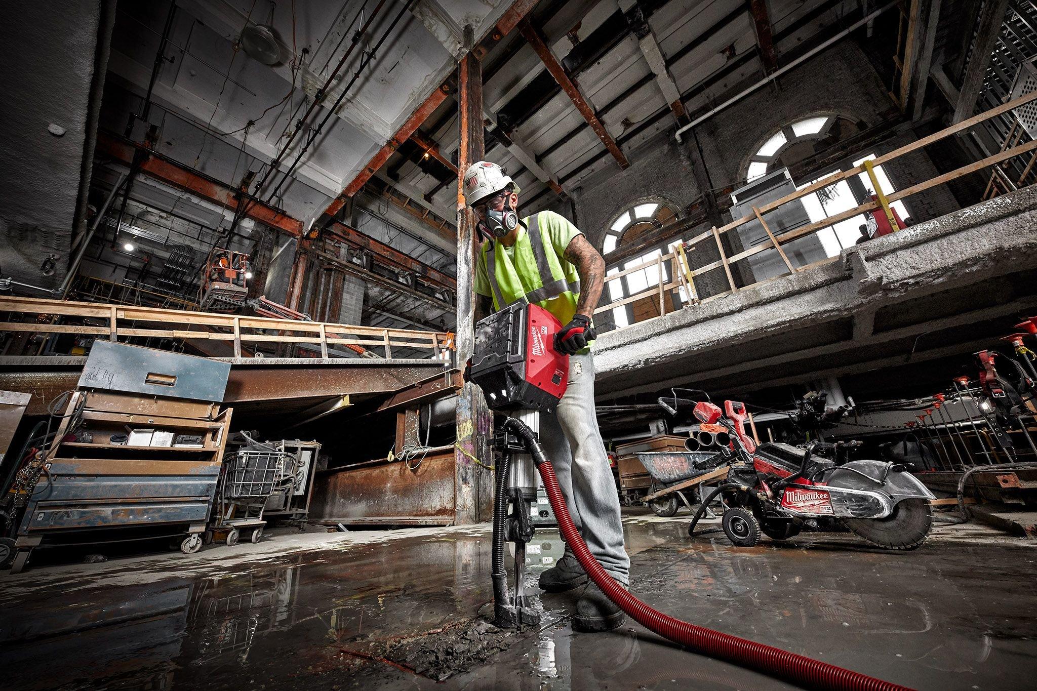 A cement mason uses a Milwaukee breaker to break up concrete floor