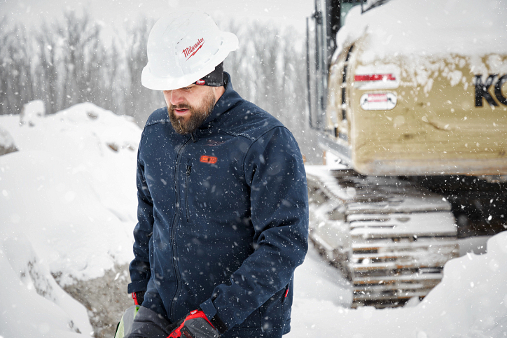 A tradesman in a navy-blue Milwaukee® heated jacket and hard hat walks across snowy jobsite beside excavator