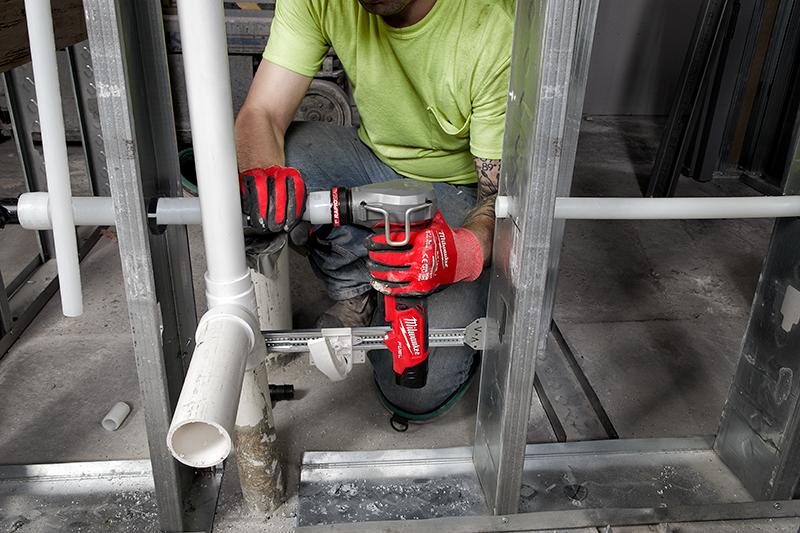 A tradesman installs PEX tubing using a Milwaukee M12 FUEL ProPEX expander