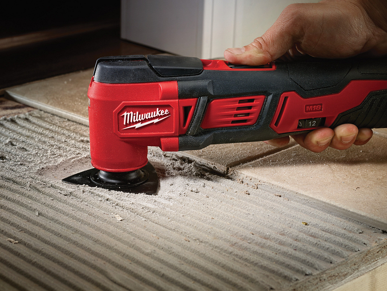 A general contractor uses an oscillating tool to install grout for tile floor