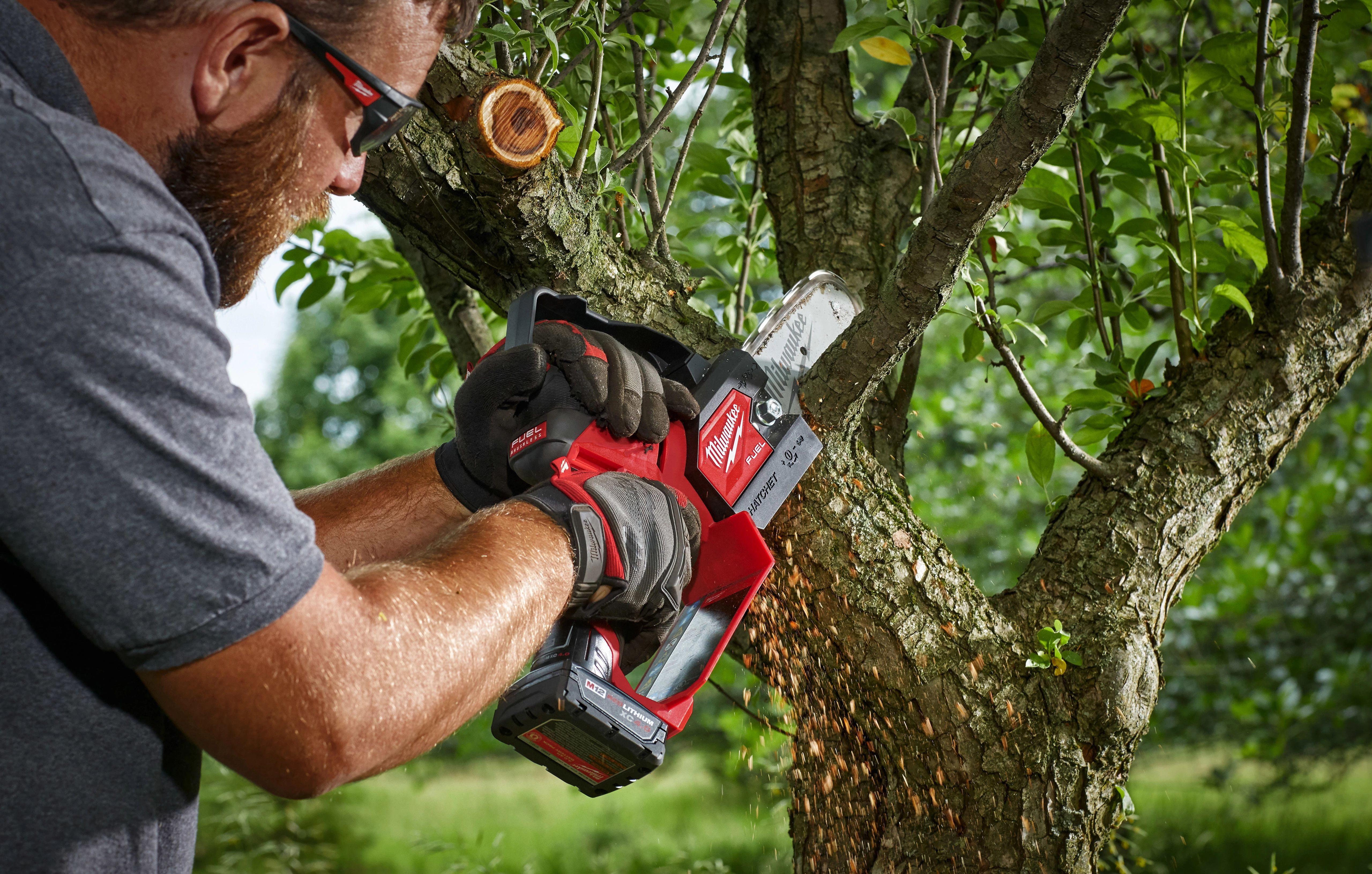 A landscape tree specialist utilizes a Milwaukee hatchet pruning saw to remove small branches in tight space