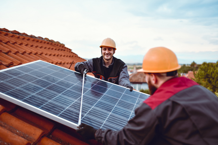Two tradesmen install a residential solar panel on a homeowner's roof