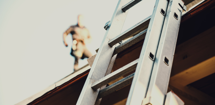 A ladder leans against roof with roofing contractor obscured in the background