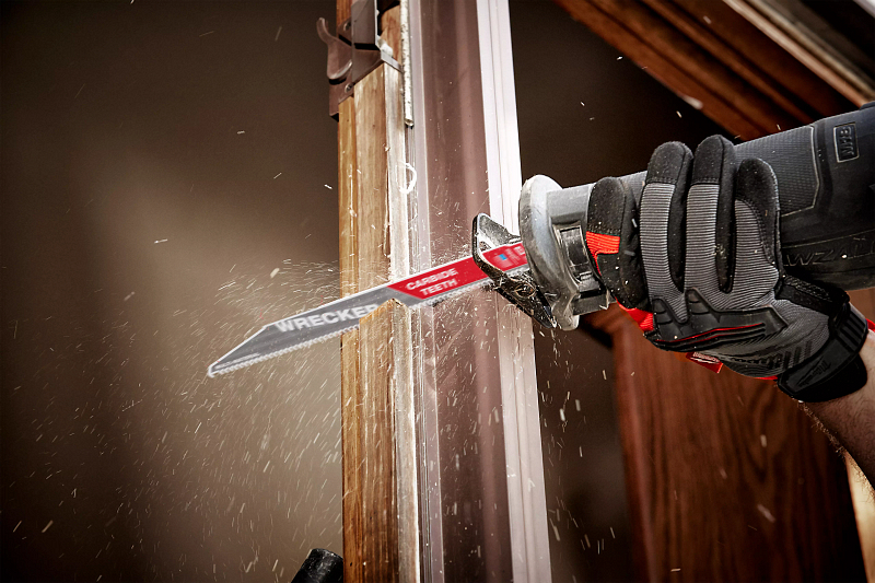 A general contractor uses a sawzall to cut through door panel