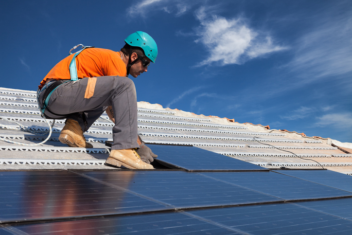 A young Solar Photovoltaic specialist installs solar panels on roof