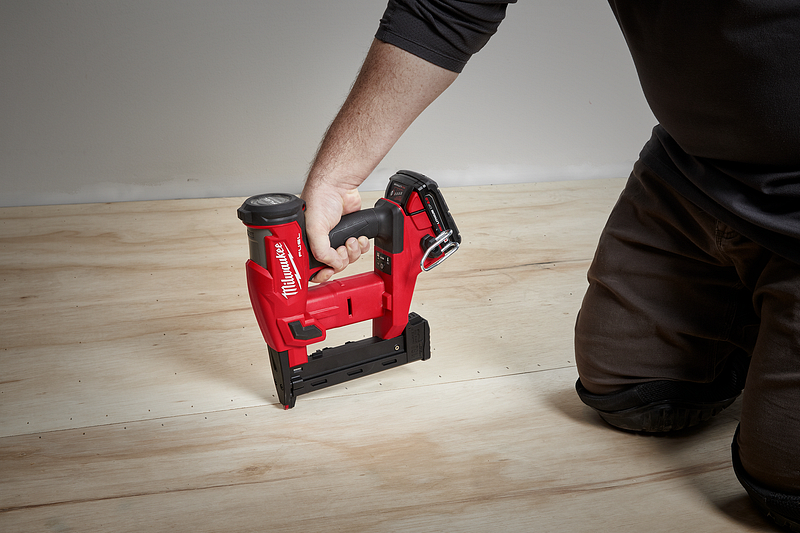 A general contractor uses a staple gun to install flooring