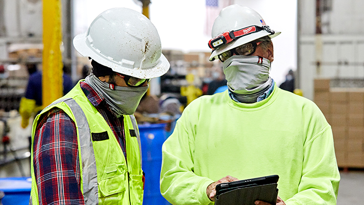 Two warehouse managers wearing gators and hard hats consult inventory over tablet device