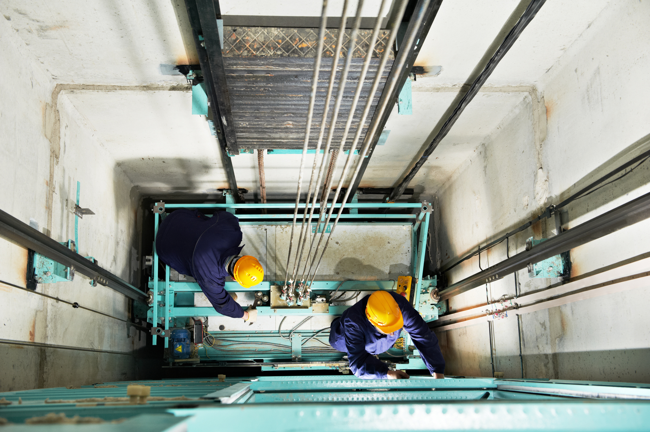 Two service technicians at the bottom of elevator shaft service hydraulics system