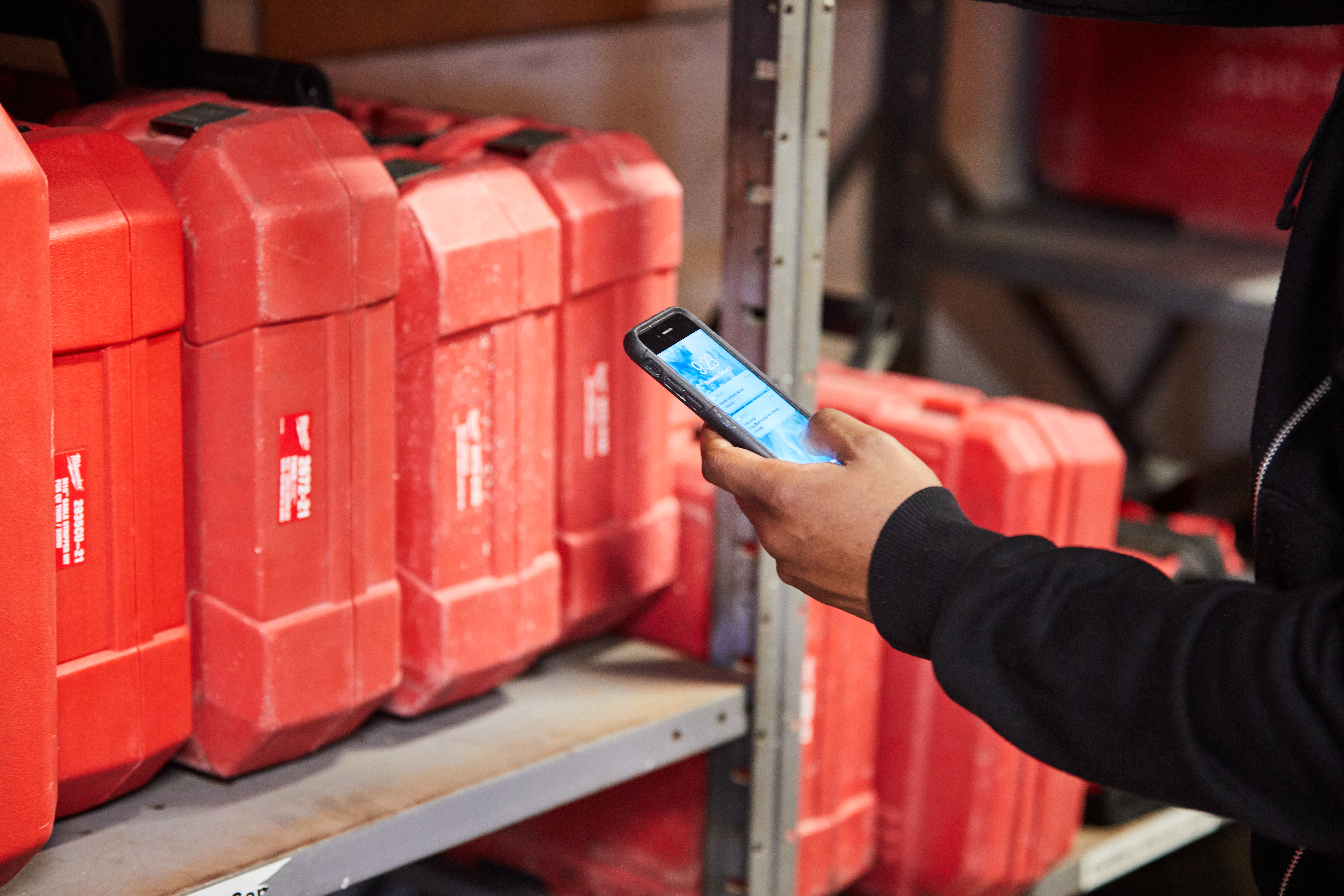 A tool crib manager among inventory shelving uses smartphone