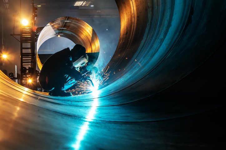 A welder fuses industrial steel plates