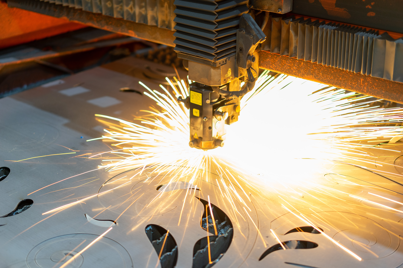 A welding robot in prefab shop cuts out precise shape in sheet metal