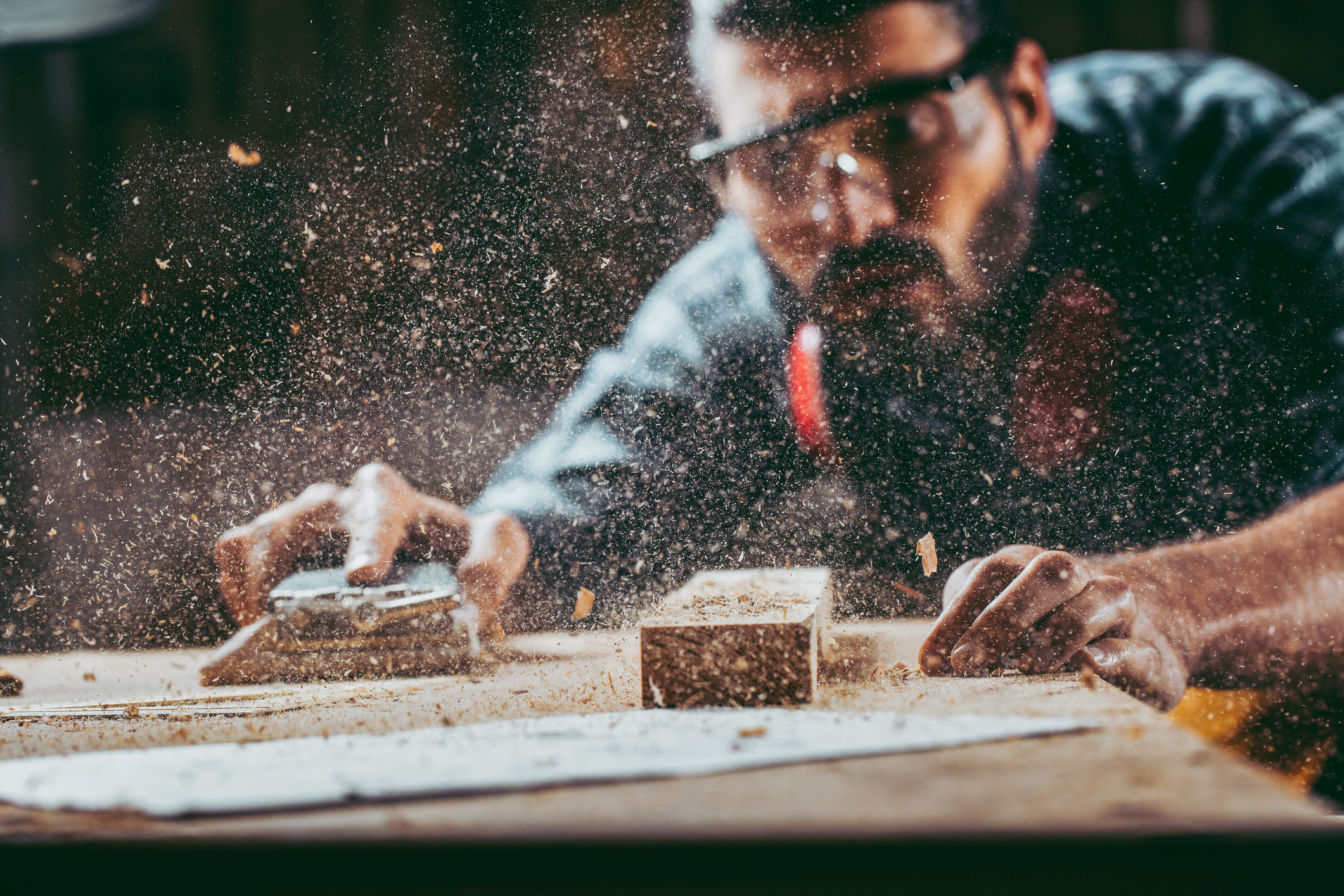 A woodworker wearing safety glasses sands down plywood sheet with sawdust filling the air in front of him
