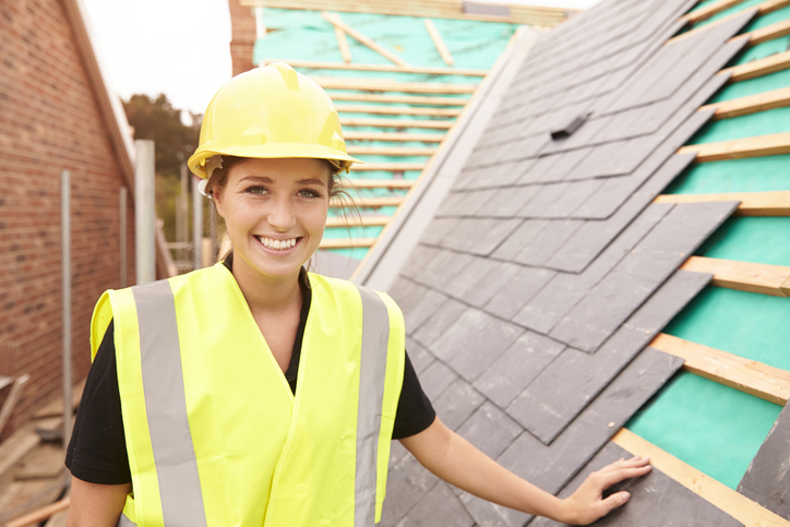 A young woman in a high-visibility vest and yellow hard hat learning the roofing trade