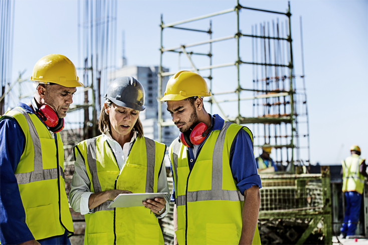 A team of construction technologists review project information on a digital tablet