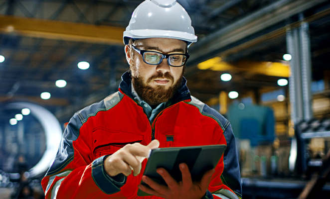 A construction technologist on a work site utilizes a digital tablet to access project information