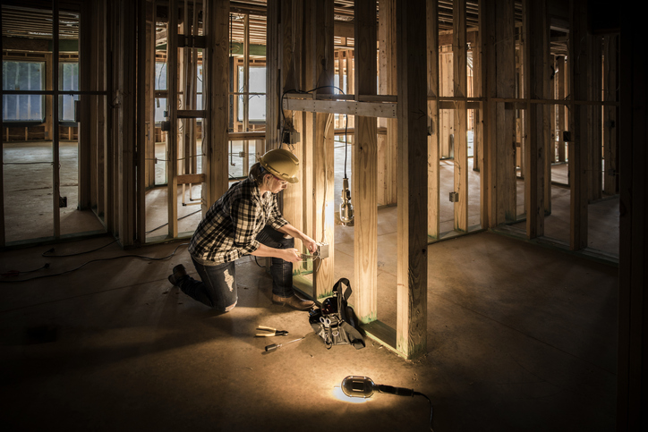 An electrician installs housing wiring on new construction