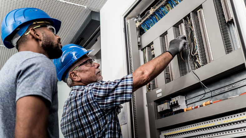 A Master Electrician demonstrates proper wiring to Apprentice